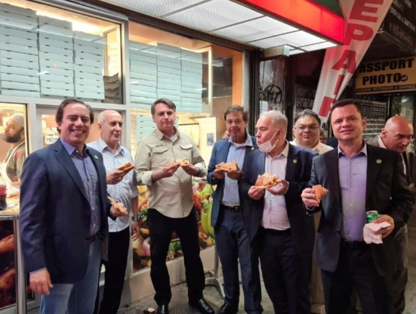 Brazil's President Jair Bolsonaro (3d L) eats pizza with Caixa Economica Federal Bank President Pedro Guimaraes, General Luiz Eduardo Ramos, Tourism Minister Gilson Machado Neto, Health Minister Marcelo Queiroga and other politicians on a street ahead of the United Nations General Assembly in New York City, U.S. September 19, 2021.