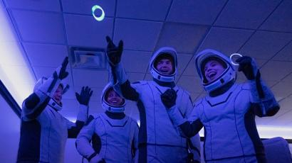 Four space tourists wear spacesuits and juggle glow rings.