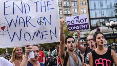 """protestors hold signs saying """"end the war on women"""" at a reproductive rights rally"""