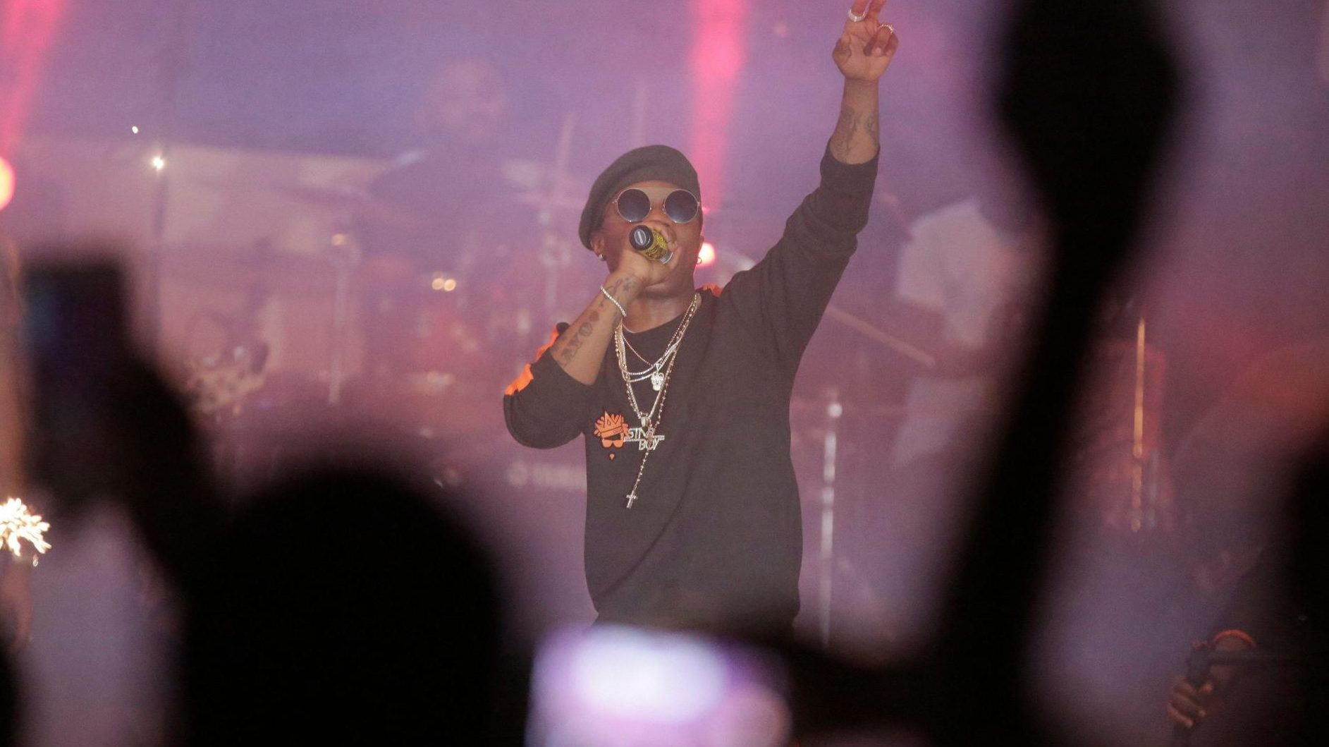 An image of Wizkid dressed in a black shirt and beret, performing at an event