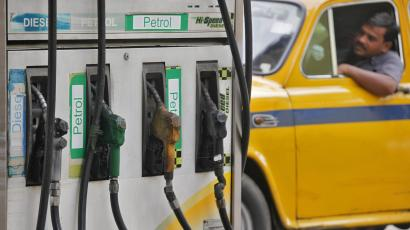 An image of a driver waits in a taxi for his turn to fill up his tank with diesel at a fuel station in Kolkata