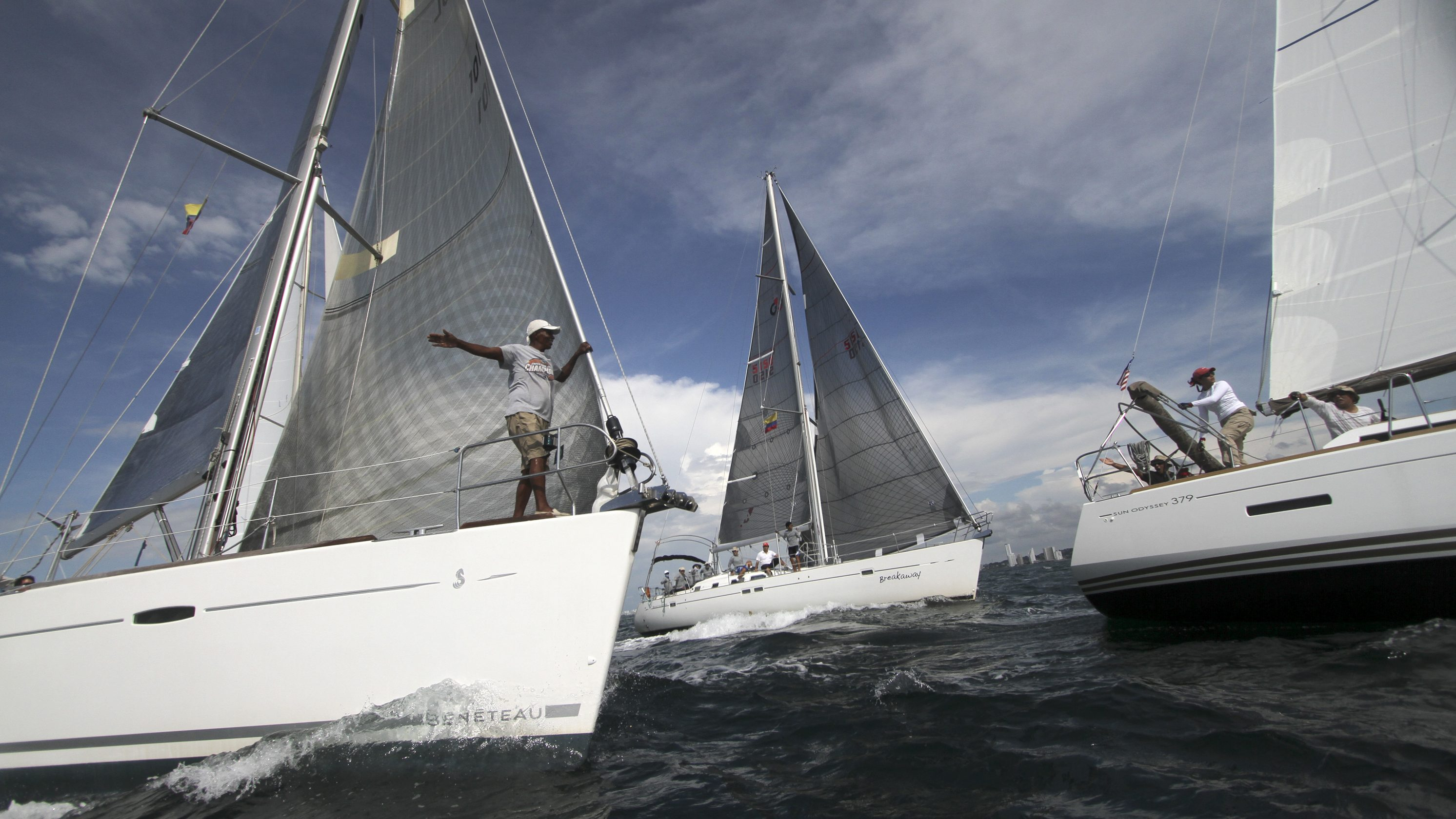 Three sailboats close to one another during a regatta