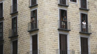 People look at the view from an apartment at Sant Jaume square at Gothic quarter in Barcelona, Spain, August 18, 2015. Barcelona's new mayor is picking a fight with home rental websites as she tries to crack down on uncontrolled tourism that she fears could drive out poor residents and spoil the Catalan capital's charm. Picture taken on August 18, 2015.