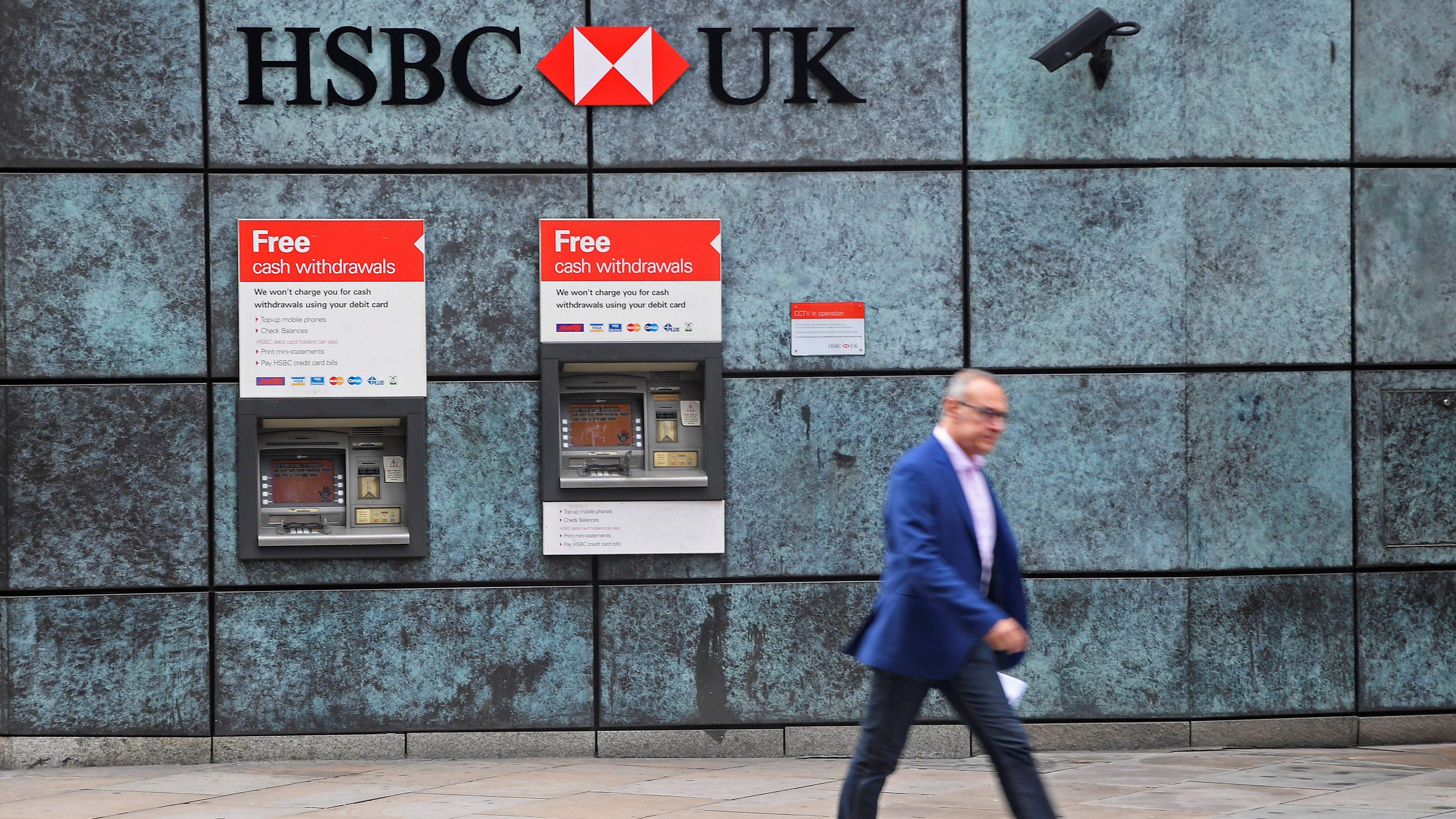 A worker walks past HSBC cash machines.