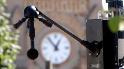 A black device with three microphones jutting out at angles from a central sphere, and one long microphone jutting out directly below are seen in the foreground in front of a clocktower in the background