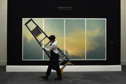 A gallery assistant removes a ladder in front of 'Wolken (Fenster) (Clouds (window))' by German painter Gerhard Richter during a media preview for 'Rembrandt to Richter' at Sotheby's auction house in London