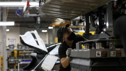 A worker looks to marry the body structure with the battery pack and the front and rear sub frames as they assemble electric vehicles at the Lucid Motors plant in Casa Grande, Arizona, U.S.