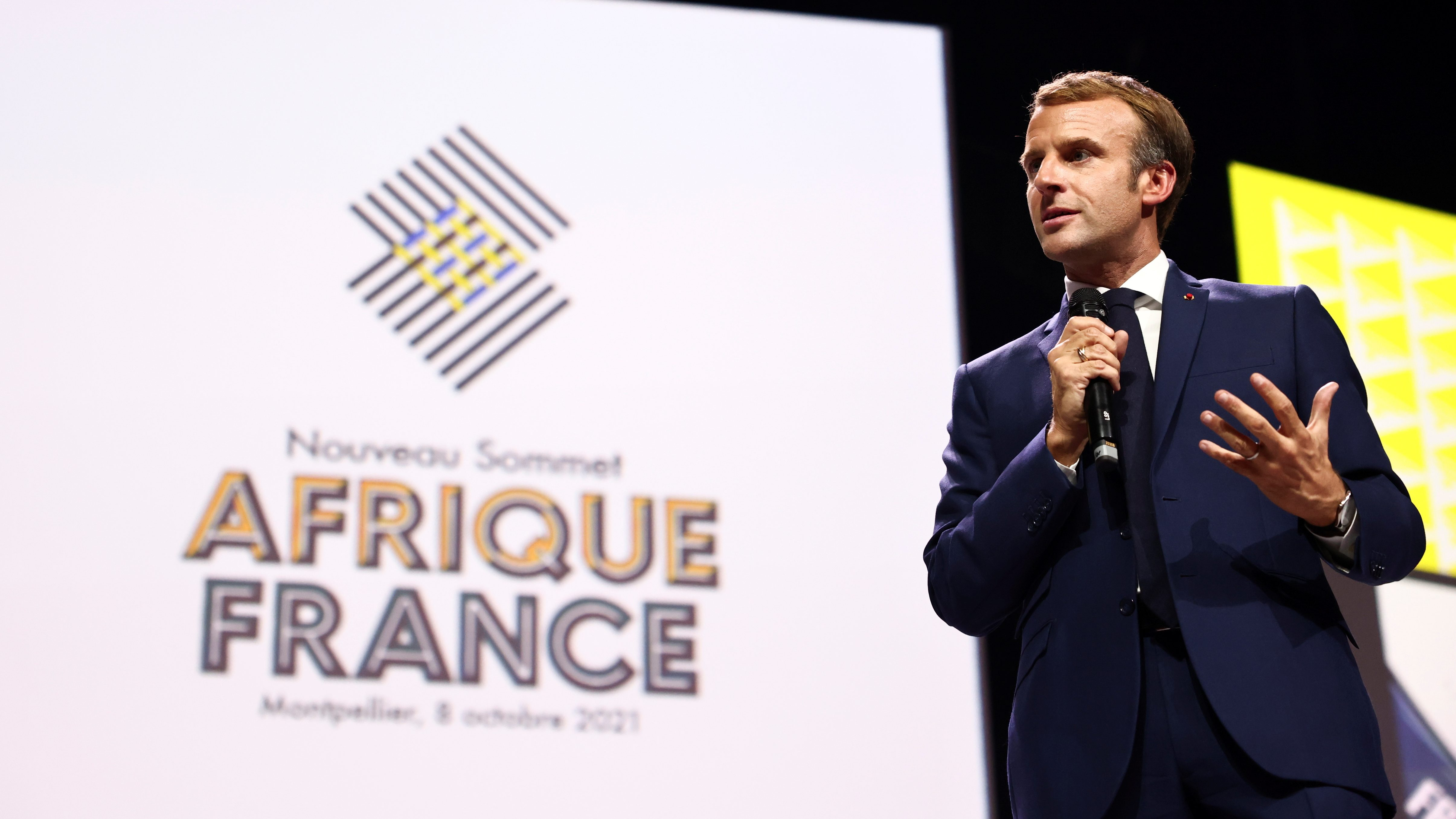 A picture of Emmanuel Macron holding a microphone on stage with a backdrop of the Africa-France summit 2021 behind him