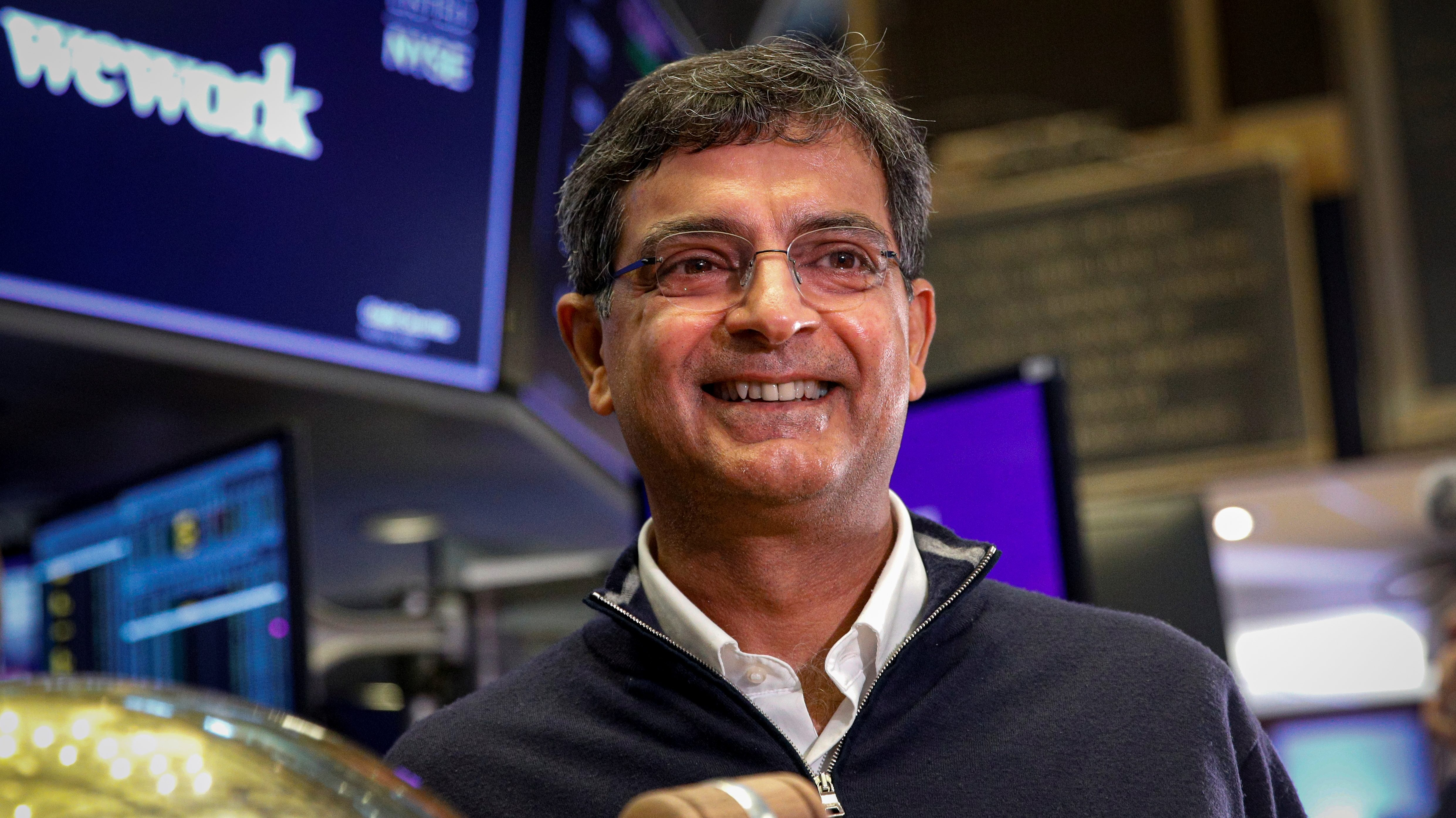 Sandeep Mathrani, CEO of WeWork, Inc. holds a gavel at his company's public debut on the floor of the New York Stock Exchange.