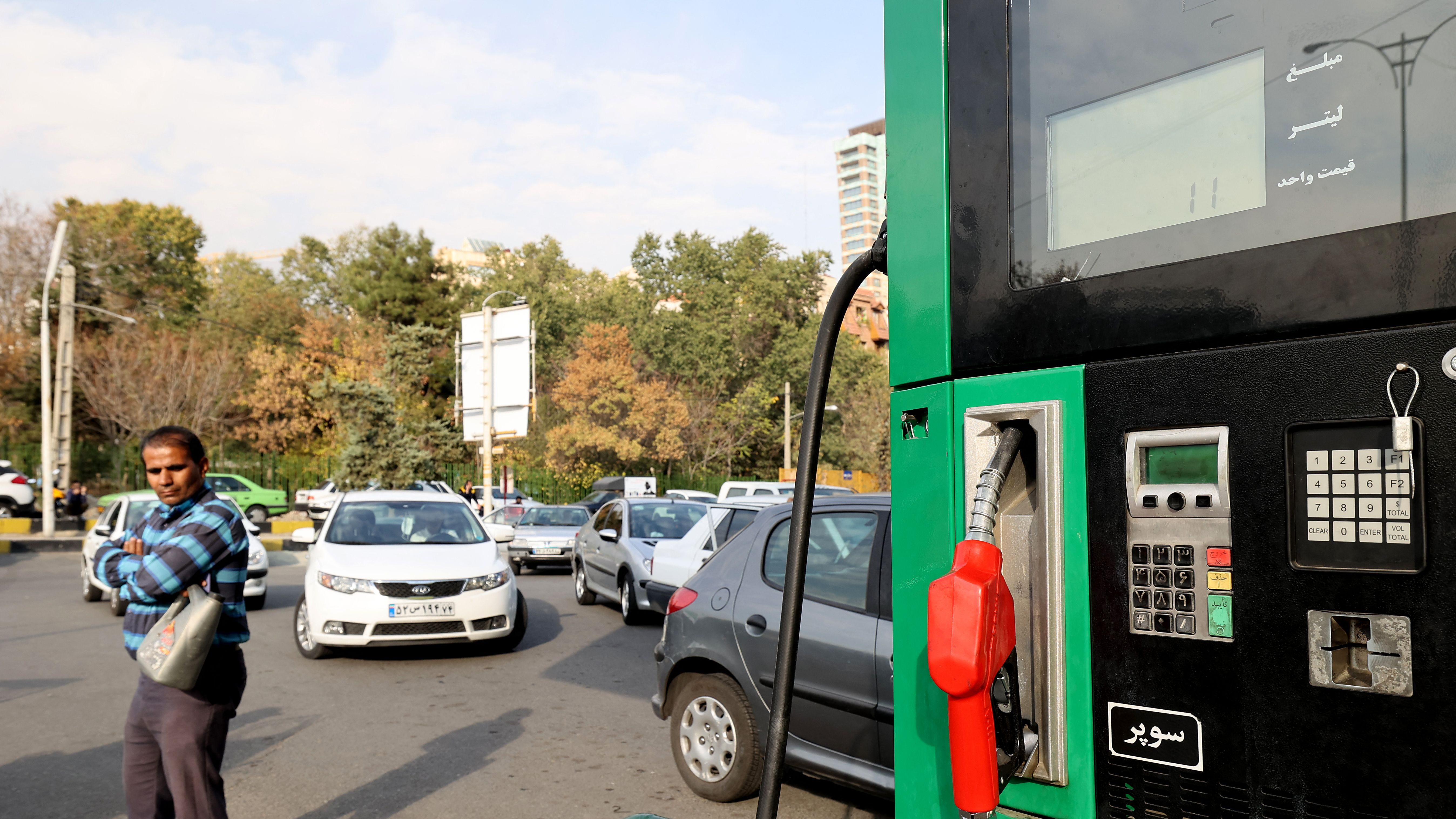 A man is standing outside of a gas pump with a container, as cars queue up behind him to fill up at a service station in Iran's capital Tehran.