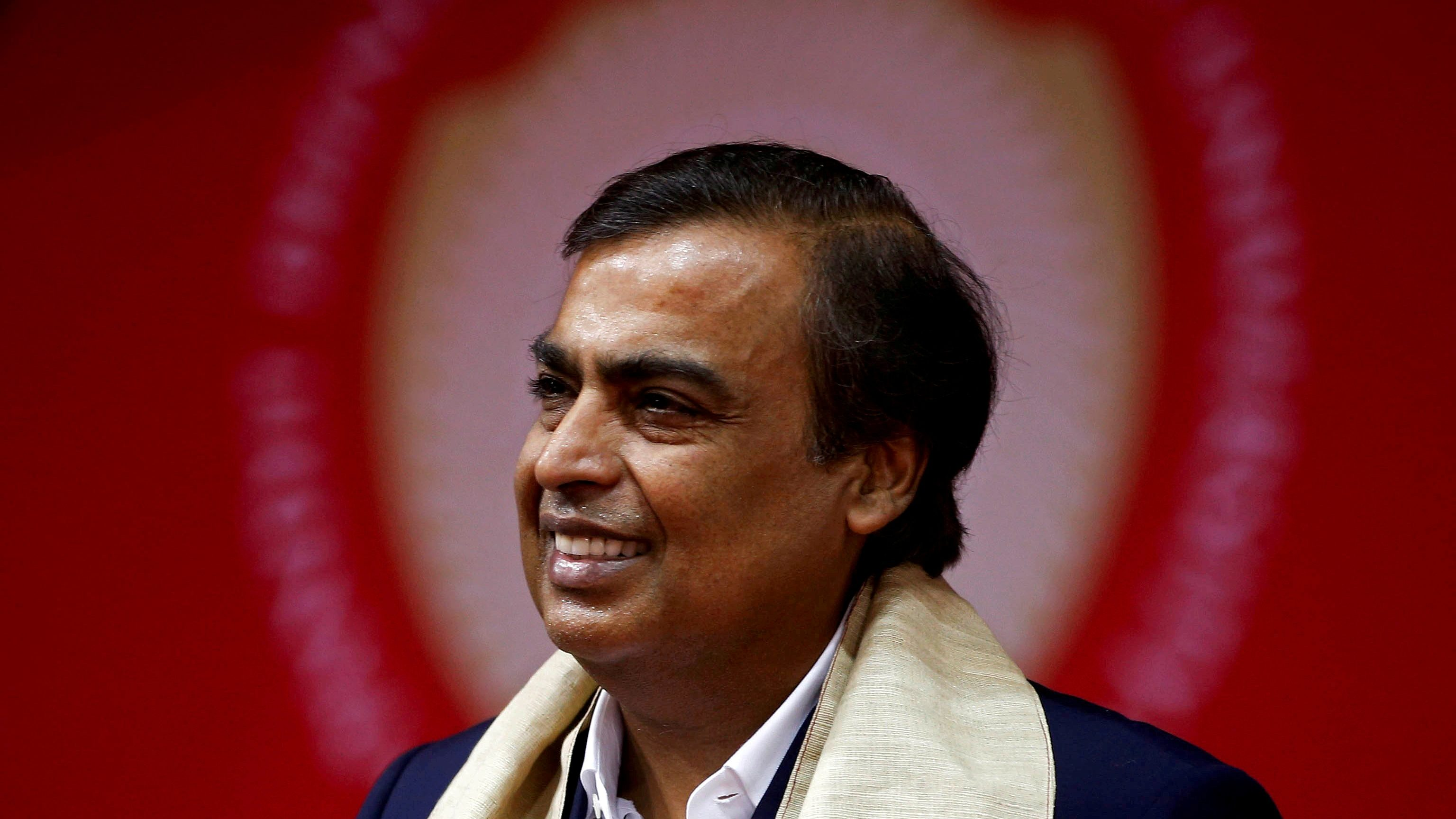 Mukesh Ambani, Chairman and Managing Director of Reliance Industries standing in front of a red banner